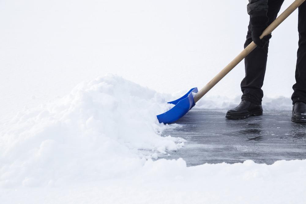 shovel snow reveals ice on driveway