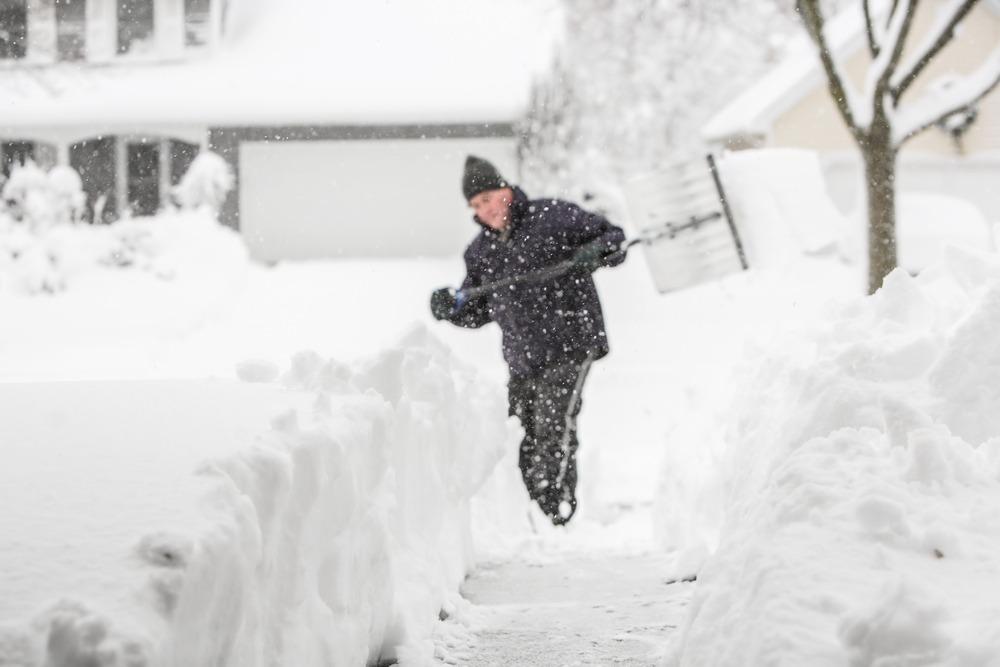 man shovels during snowstorm in ottawa canada